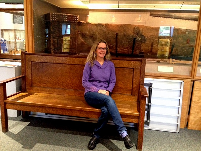 Museum Director, Kathi Riemer, sits in front of a display featuring an undated bentwood box. Photo/Angela Denning
