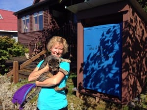 Jo Ann Day hold her cat, Bella, next to her lending library. Photo/Angela Denning