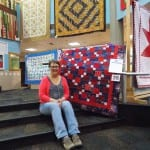 Carol Kandoll sits next to a Quilt of Valor at the quilt show in the Petersburg High School lobby, Oct. 22. Photo/Angela Denning