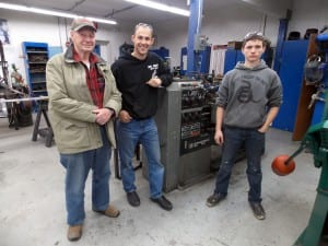Former PHS shop teacher, Bill Neumann, current shop teacher, Dave Owens, and Sophomore shop student, Sebastian Davis stand next to the lathe machine in the high school shop. Photo/Angela Denning
