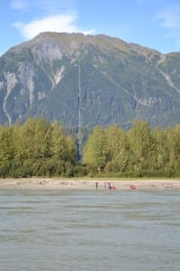 Kayakers rest near the U.S.-Canadian border on the Stikine River, marked by a line of cleared trees. (KFSK file photo)