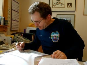 Dave Berg looks over a spread sheet of this year's visitors at Viking Travel, Inc. Photo/Angela Denning