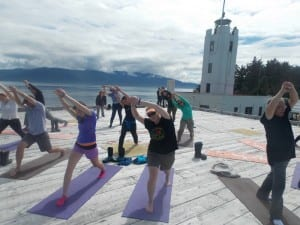 Cruise ship tourists practice yoga in front of the backdrop of Five Finger Lighthouse.(Joe Sykes)