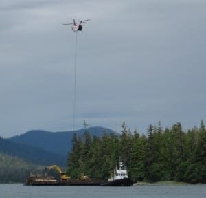 A helicopter loads a log onto a barge during a University of Alaska timber sale on western Mitkof Island in 2014 (KFSK file photo)